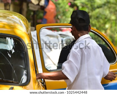 A taxi driver is opening the door to help his passengers to get into the car stock photograph #1025442448