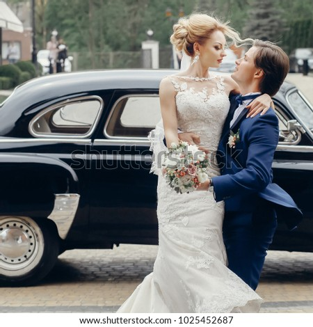luxury wedding couple dancing at old car in light. stylish bride and groom hugging and embracing in city street. romantic sensual moment. woman looking at man #1025452687
