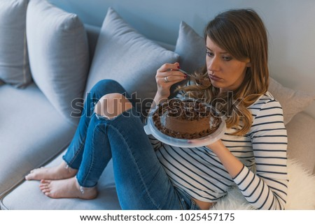 Depressed woman eats cake.  Sad unhappy woman eating cake. Sad woman eating sweet cake. Close up of woman eating chocolate cake. food, junk-food, culinary, baking and holidays concept  #1025457175