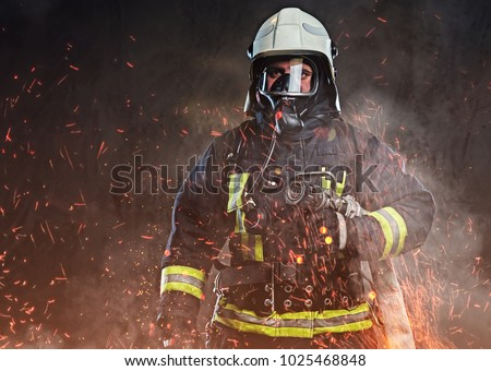 A firefighter dressed in a uniform in a studio. Royalty-Free Stock Photo #1025468848