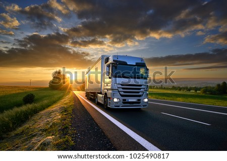 Truck driving on the asphalt road in rural landscape at sunset with dark clouds #1025490817