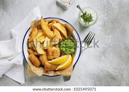 Fish and chips. Traditional british hot dish consisting of fried fish, potato chips, mushy peas and tartare sauce.