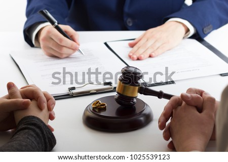 Hands of wife, husband signing decree of divorce, dissolution, canceling marriage, legal separation documents, filing divorce papers or premarital agreement prepared by lawyer. Wedding ring #1025539123