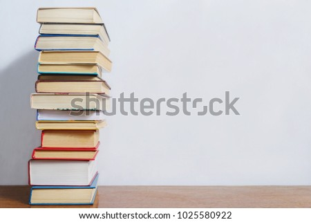 A stack of different books on a table against a white wall background #1025580922