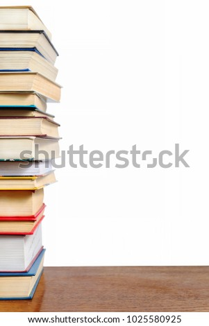 A stack of different books on a table against a white wall background #1025580925