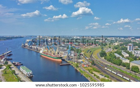 Panoramic view of Riga city - capital of Latvia. View over Daugava River, towards a harbour. Railway seen on the right. #1025595985