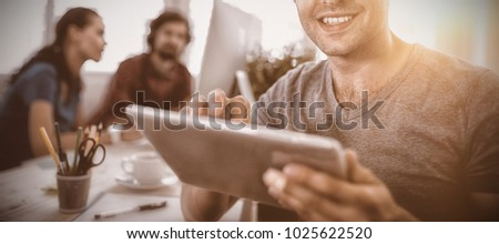 Portrait of smiling business executive using digital tablet in office #1025622520