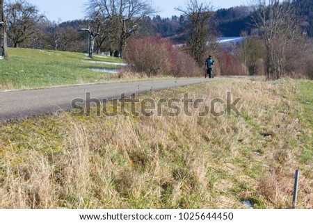 senior man with rollator on a bikeway and sunny winter day with blue sky in south germany #1025644450