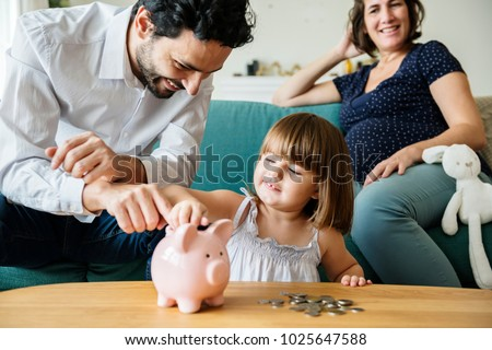 Family saving money in piggy bank Royalty-Free Stock Photo #1025647588