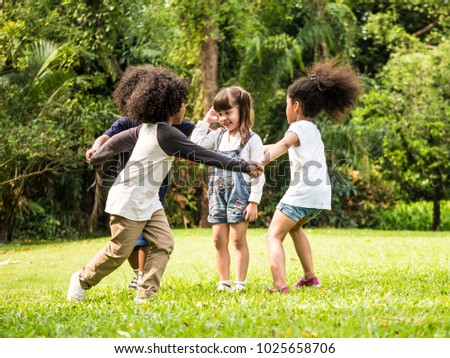 Group of children playing together in the park #1025658706