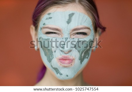 Emotional portrait of a jolly and sexy young woman with a cosmetic mask of blue clay on her face, looking into the camera wrinkling her forehead and nose against the red wall.