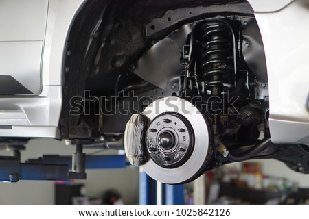 Car service - mechanic unscrewing automobile parts while working under a lifted auto.Disc car close up Royalty-Free Stock Photo #1025842126