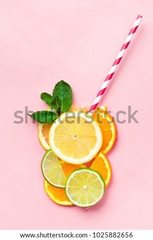 Glass of juice made of citrus slices with mint leaves and a straw on light pink background. Citrus juice concept #1025882656