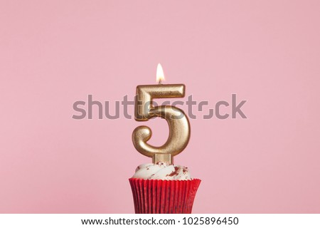 Number 5 gold candle in a cupcake against a pastel pink background #1025896450