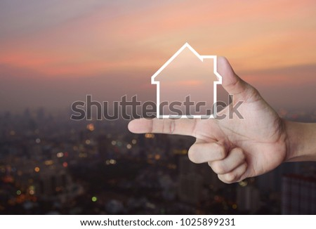 House icon with copy space on finger over blur of cityscape on warm light sundown, Real estate concept #1025899231