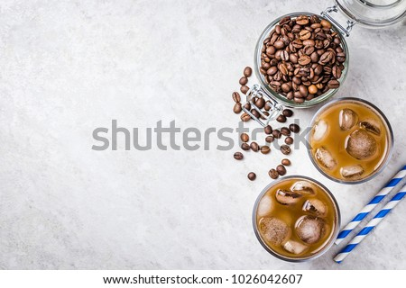 Cold brewed iced coffee in glass and coffee beans in glass jar on white background. Top view, copy space. #1026042607