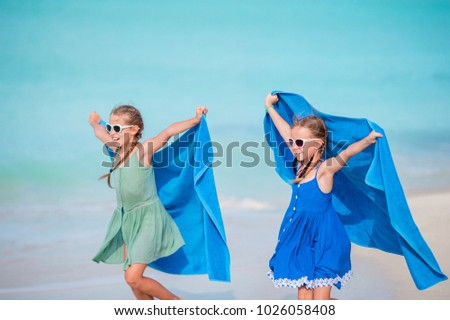 Little girls have fun with beach towel during summer vacation #1026058408