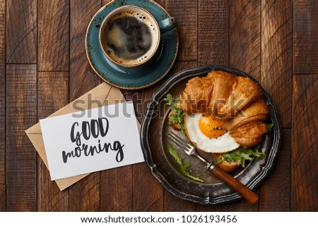"Croissant sandwich with fried egg and arugula, cup of coffee and greeting card ""good morning"" on wooden background. Flat composition. Delicious and healthy breakfast"