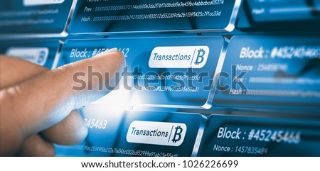 Finger pressing a block chain block with the text transaction, a bitcoin symbol and security sha256 algorithm hach. Composite between a hand photography. Royalty-Free Stock Photo #1026226699