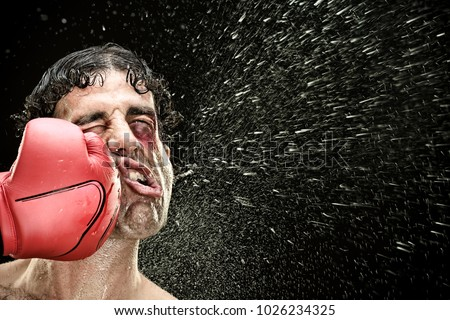 silly boxer man takes a punch in the face isolated on black.funny concept portrait Royalty-Free Stock Photo #1026234325