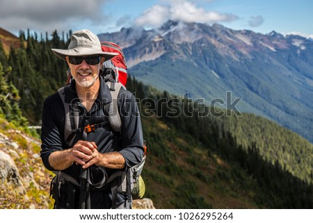 Hiker poses in front of mountain peaks range hiking backpacker old older aarp strong strength vital energetic landscape photography portrait background colorful adventure retired retirement outdoor  Royalty-Free Stock Photo #1026295264