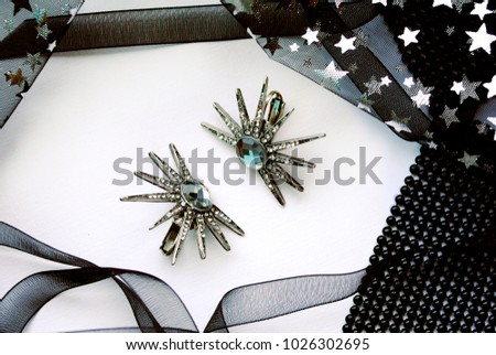 Pair of star designed metal earrings with light blue crystal surrounded by black ribbon and black fabric with stars on the white background #1026302695