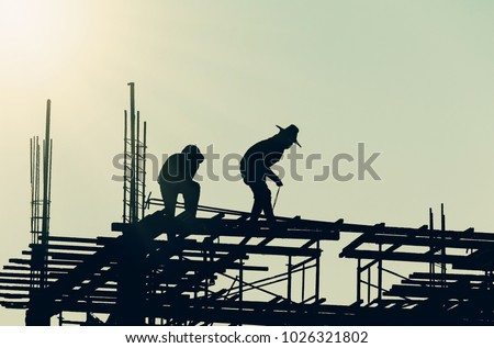 Silhouette City worker, construction crews to work on high ground heavy industry and safety concept over blurred natural background sunset  #1026321802