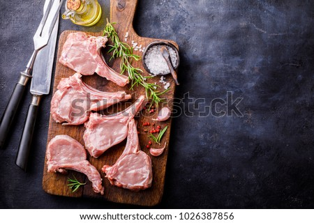 Meat Raw Fresh Mutton on the bone Spices Chesno and Rosemary on a black background Copy space for Text  #1026387856