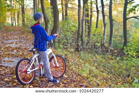 A young cyclist stands on a sunny day by bicycle in the nature #1026420277