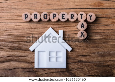 Elevated View Of House Model Near Blocks With Property And Tax Text On Wooden Background #1026630460