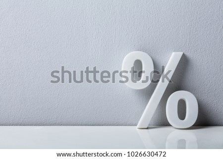 Close-up Of A Percentage Sign Leaning On White Wall #1026630472