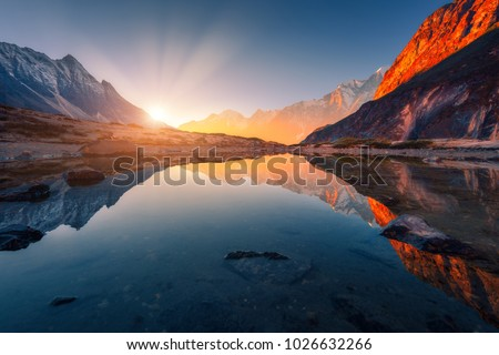 Beautiful landscape with high mountains with illuminated peaks, stones in mountain lake, reflection, blue sky and yellow sunlight in sunrise. Nepal. Amazing scene with Himalayan mountains. Himalayas #1026632266