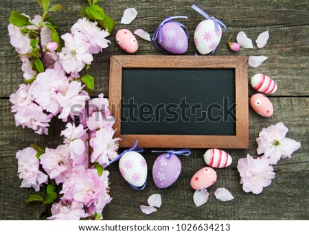 Easter eggs and sakura blossom on a old wooden background