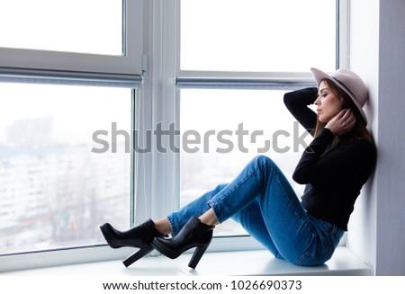 Beautiful boho woman in wool hat sitting by the window #1026690373
