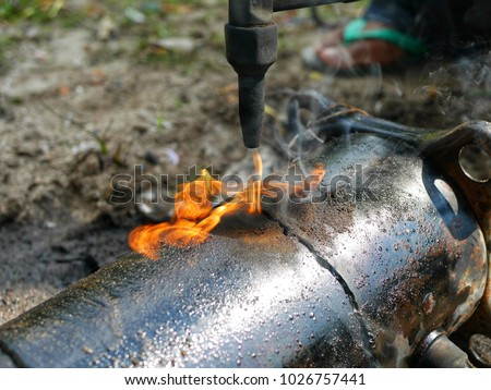 employees in the shop to buy gas spray gun.to cut the compressor is broken.to separate between copper and steel apart.to recycle Royalty-Free Stock Photo #1026757441