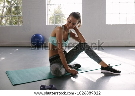 Female athlete sitting on exercise mat at gym and smiling. Fit young woman taking break after her workout at health club. #1026889822