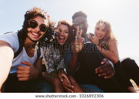 Excited young friends taking selfie outdoors. Diverse group of men and women sitting together and taking self portrait on their holiday. #1026892306