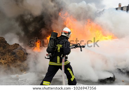 firefighter extinguishes a fire Royalty-Free Stock Photo #1026947356