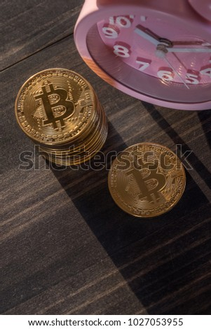 Bitcoin with an alarm clock on wooden table top  #1027053955