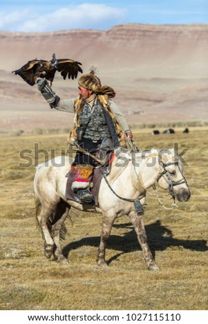 SAGSAY, MONGOLIA - SEP 28, 2017: Berkutchi (Eagle Hunter) on the horse while hunting to the hare with a golden eagles on his arms in the mountains of Bayan-Olgii aimag.  #1027115110