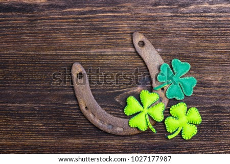 Rusty horseshoe and felt clover leaves on wooden boards. St.Patrick's day holiday symbol. Lucky charms. Space for text. #1027177987