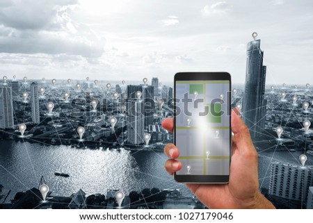 Hand holding mobile phone on blue tone smart city with GPS icon and network connections background, communication network technology concept #1027179046