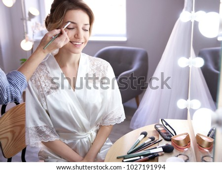 Makeup artist preparing bride before her wedding in room #1027191994