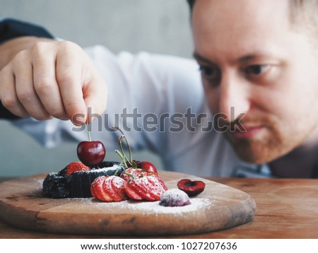 Close up pastry chef decoration delicious dessert dish,he putting cherry and some cocoa powder on top before serving for customers in bakery. #1027207636