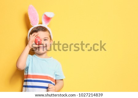 Cute little boy with bunny ears holding Easter egg on color background