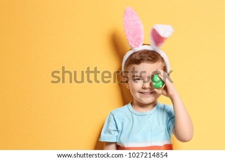 Cute little boy with bunny ears holding Easter egg on color background #1027214854