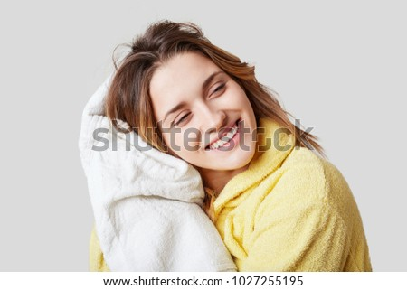 Positive female in bathrobe, holds white towel, rests after taking showr alone, poses against white background, has cheerful expression. Beauty treatments and positiveness concept. Wellbeing #1027255195