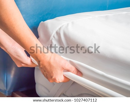 Woman is putting the bedding cover or mattress pad on the bed or putting off for cleaning process. #1027407112