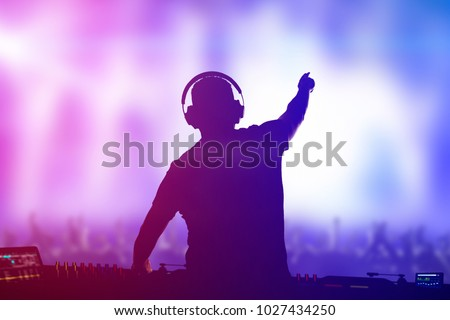 Charismatic disc jockey. Club, disco DJ playing and mixing music for crowd people. Royalty-Free Stock Photo #1027434250