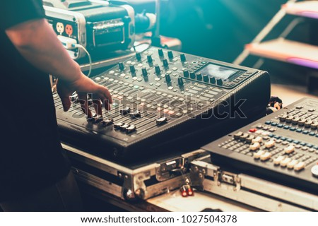 professional stage sound mixer closeup at sound engineer hand using audio mix slider working during concert performance Royalty-Free Stock Photo #1027504378